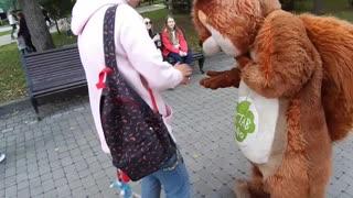A kind girl feeds a squirrel )