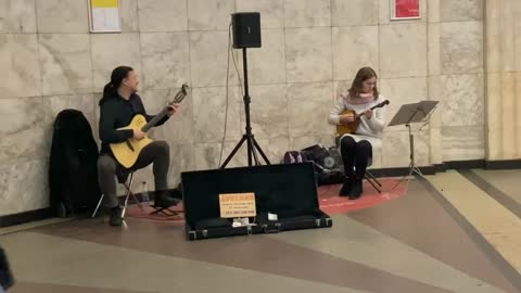musicians on the subway play the violin