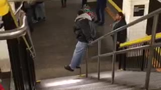 Man slides down staircase handrail in subway station