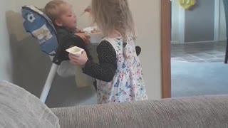 Little lady feeding her baby brother