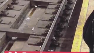 Worker trying to pick up white headphones from train track with claw