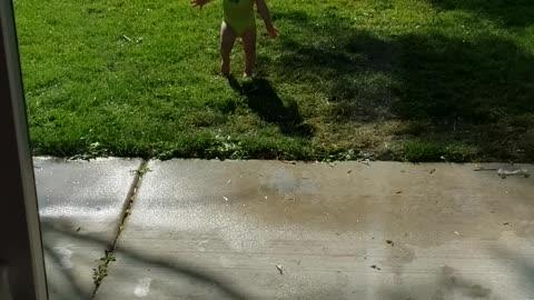 1 year old excited in sprinklers