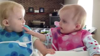 Twins biting each other fingers
