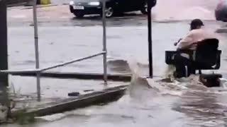 Fearless person on a motorized scooter during a flood