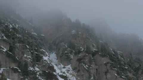 Snow falling by a mountain side
