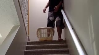 Guy slides down his stairs in a laundry basket and falls down stairs
