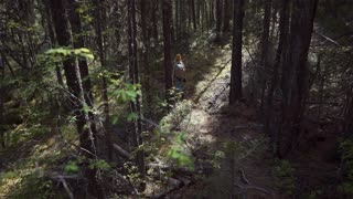 A Woman Walking in the Middle of the Forest