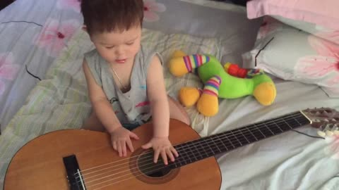 Cute little boy is playing guitar