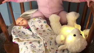 Tiny toddler rocks baby doll to sleep