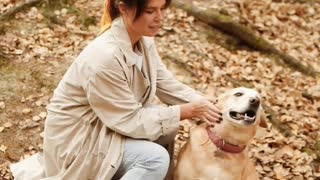 Young woman petting her dog outdoors
