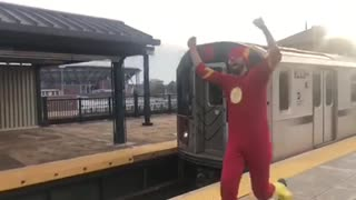 Man in red flash costume running next to subway train