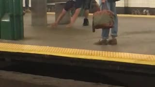 Man in black shirt does yoga stretches in subway station