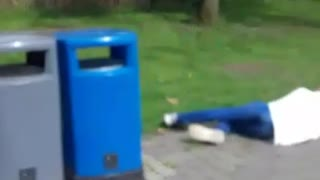 Man in white jumps over blue trash bin and falls forward