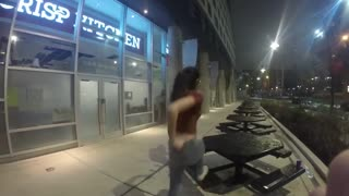 Girl dances with friends, climbs up on outside table, slips, and falls off
