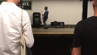 Man playing guitar on other side of tracks