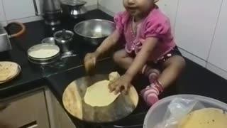 little baby making food (roti)