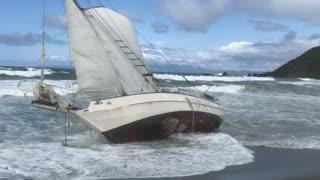 Sailboat stuck on shore beach water