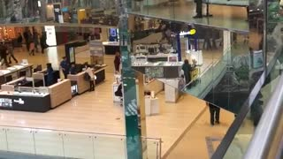 Two guys jump over railing mall into pool water