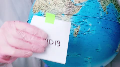 People With Face Masks and Latex Gloves Holding a Globe Uploaded at April 17, 2020