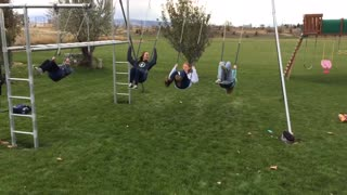 Four girls back flip on swings one falls