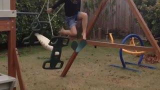 Little girl on green backyard kid swing falls off