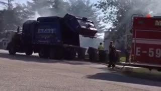 Garbage Truck Dumps Burning Load into Fire Station Parking Lot
