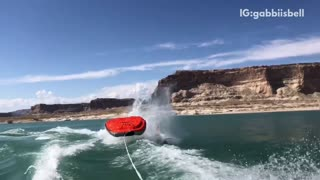 Slow motion three people fall off of red black raft lake