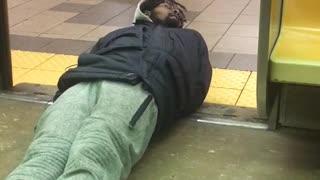 Man on floor crawls falls off subway