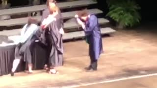 Guy walking across graduation stage trips and falls
