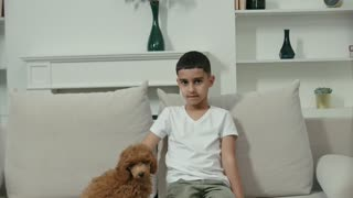 A Boy Petting His Dog While Sitting in a Couch