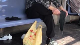 Man rubs bare foot on subway train