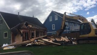 Excavator destroys house