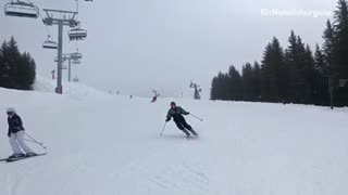 Woman skiing black jacket with green falls in front of camera