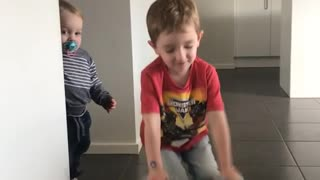 Little boy says abracadabra and does disappearing blanket magic trick with a gray fur blanket