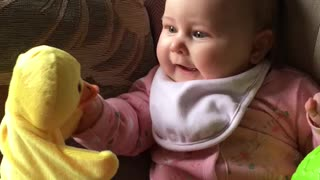 Baby preciously giggles at duck hand puppet