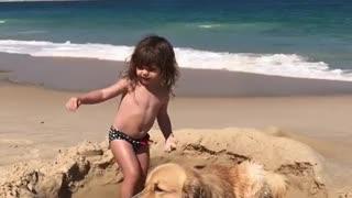 Golden Retriever becomes part of little girl's sandcastle