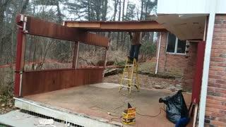 Man saws wooden board in half, wall falls and knocks ladder down, man falls off