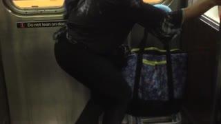 Blonde woman dancing next to subway train door