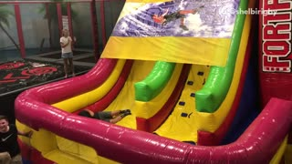 Guy on blow up slide falls off the cover and falls down slide