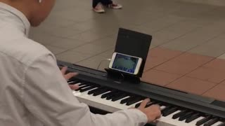 Man playing piano while playing games on phone