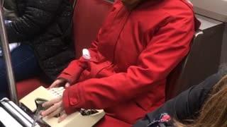 Woman uses typewriter on a subway train