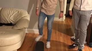 Brown shirt guy living room falls off skateboard