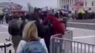 Americký policista ukazuje lidem, aby šli dál a zve je do Kongresu