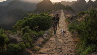 Man Running with a Dog on Mountain Top