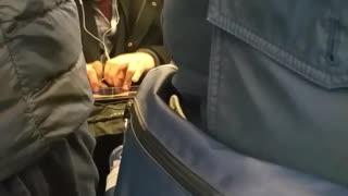 Man plays guitar on his ipad on subway