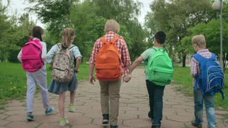 Children Walking On A Paved Pathway With Their Backpacks