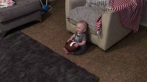 Giggling baby finds daddy's football noises hilarious