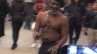 Shirtless man dances to drum beat at subway station