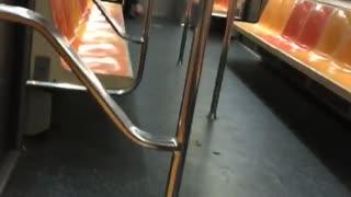 Man picking his bare feet on empty subway train