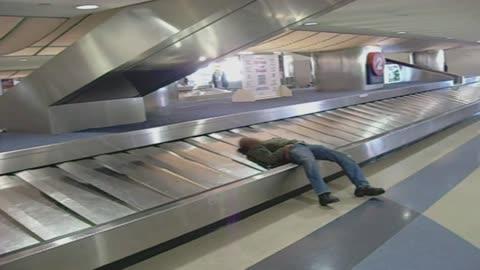 Sleeping Man Takes A Ride On Baggage Claim